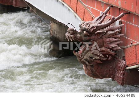 River flowing under a bridge with a dragon head 40524489