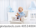 Baby boy with bottle drinking milk or formula 40534004