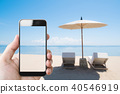 hand holding mobile smartphone on the beach 40546919