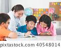 Asian teacher helps young school kids in class. 40548014