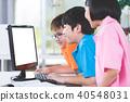 Smiling asian pupils using a desktop computer. 40548031