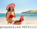 Fashionable young woman talking on mobile phone at the beach 40555112