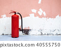 Old and Rusty Fire Extinguisher on the Ground. 40555750