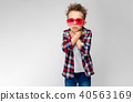 A handsome boy in a plaid shirt, gray shirt and jeans stands on a gray background. A boy in red 40563169