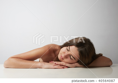 Fashion portrait of a beautiful smiling woman with long hair sleeping on the table over empty light 40564087