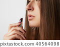 Close-up Fashion portrait of a beautiful smiling woman with long hair holding red lipstick in hands 40564098