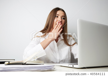 Beautiful young woman in a white shirt working on laptop over empty light background. Horizontal. 40564111