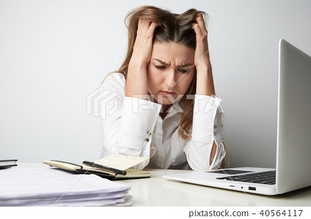 Close-up of Tired beautiful young woman in a white shirt working on laptop over empty light 40564117
