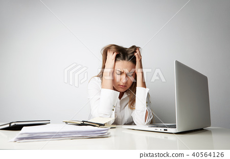 Tired beautiful young woman in a white shirt working on laptop over empty light background 40564126