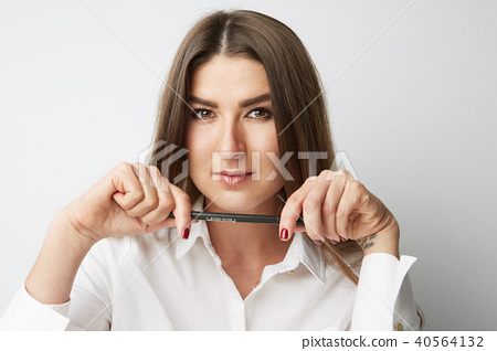 Closeup portrait of Beautiful young woman in a white shirt holding pen hands and looking at the 40564132