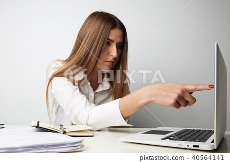 Beautiful young woman in a white shirt working on laptop and pointing finger on screen over empty 40564141
