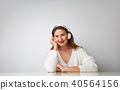 Smiling beautiful young woman listening to music on headphones over empty light background at studio 40564156