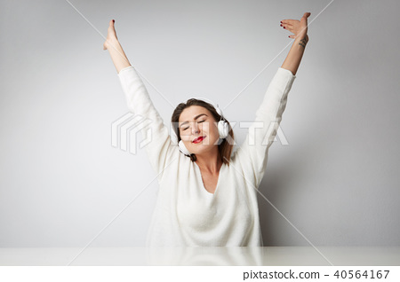 Smiling beautiful young woman listening to music on headphones over empty light background at studio 40564167