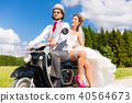 Bridal pair driving motor scooter wearing gown and suit 40564673