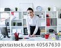 A young girl stands in the office near the table and glues stickers in the documents. 40567630