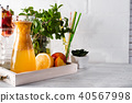 Orange lemonade in the decanter on a wooden tray with ftuits and mint 40567998