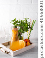 Orange lemonade in the decanter on a wooden tray with ftuits and mint 40568001