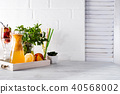 Orange lemonade in the decanter on a wooden tray with ftuits and mint 40568002