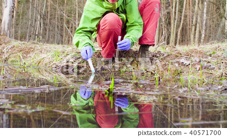 Scientist ecologist in the forest taking samples of water 40571700