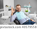 Male is smiling to the camera and showing ok sign being satisfied after teeth treatment in a modern 40579558