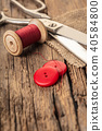 red thread with buttons and scissors 40584800
