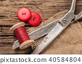 red thread with buttons and scissors 40584804