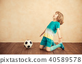 Child is pretending to be a soccer player 40589578