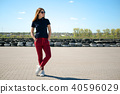 Stylishly dressed young woman in glasses stands in the middle of a stone square against the 40596029