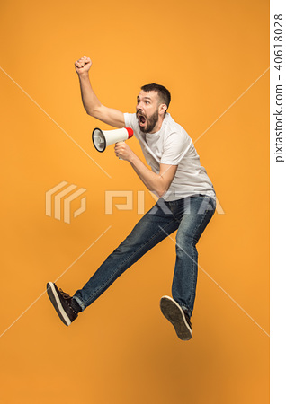 Jumping fan on orange background. The young man as soccer football fan with megaphone 40618028