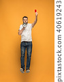 Football supporter with red card on orange background 40619243