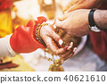Indian bride ties with holy thread on her wrist 40621610
