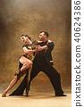 Dance ballroom couple in gold dress dancing on studio background. 40624386