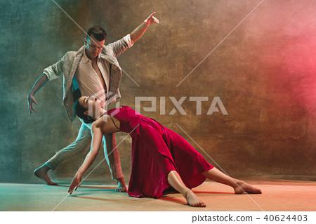 Flexible young modern dance couple posing in studio. 40624403