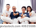 Asian grown family showing thumbs up at home 40635686