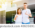 Asian couple standing with their new house 40635691