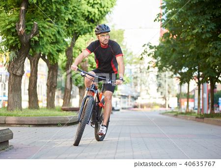 Cyclist riding along empty city streets 40635767