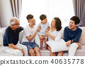 Happy Asian extended family sitting on sofa 40635778