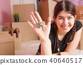 Image of young brunette with keys from apartment against blank wall 40640517