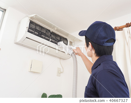 Worker cleaning the air conditioner - Stock Photo [40667327