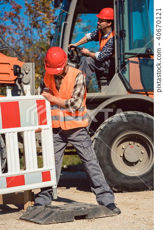 Worker setting up earthworks construction site 40670121