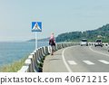 Man with his son on their shoulders walks along 40671215
