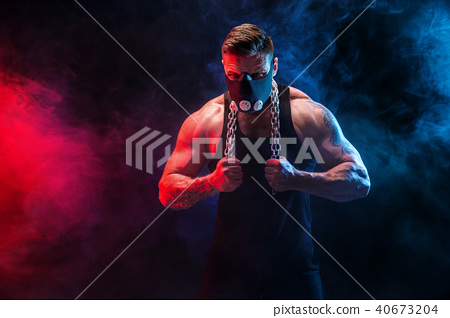 Strong male athlete in a black training mask on a black background 40673204