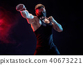 Strong male athlete in a black training mask on a black background 40673221