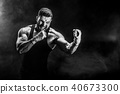 Sportsman muay thai boxer fighting on black background with smoke. 40673300