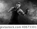 Sportsman muay thai boxer fighting on black background with smoke. 40673301
