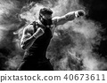 Strong male athlete in a black training mask on a black background 40673611