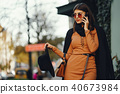 stylish girl walking through the city while using her phone 40673984