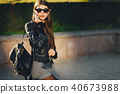 stylish girl walking through the city while using her phone 40673988