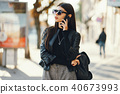 stylish girl walking through the city while using her phone 40673993