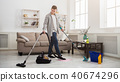 Young man cleaning house with lots of tools 40674296